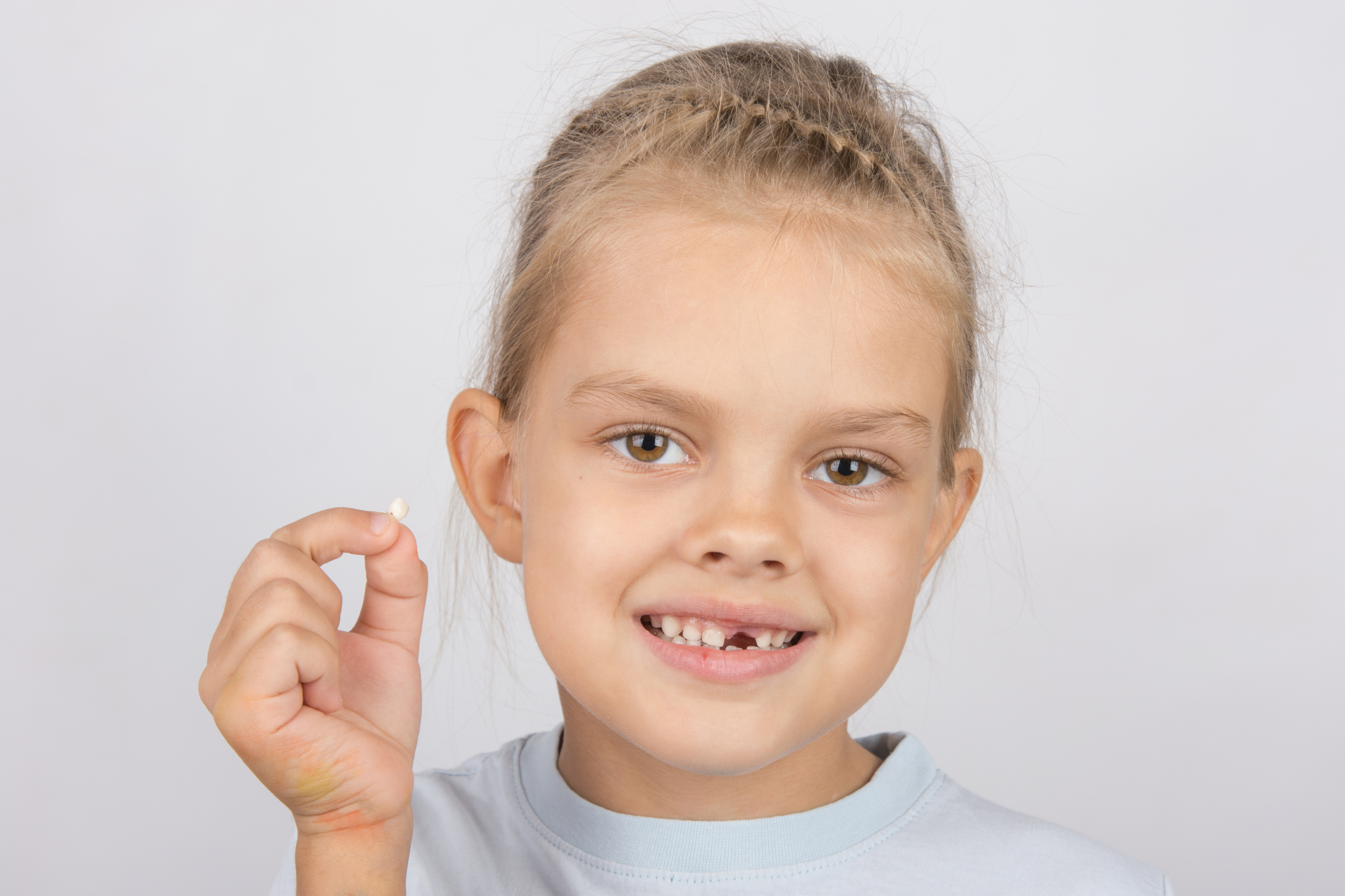 Portrait of girl with a fallen tooth in his hand